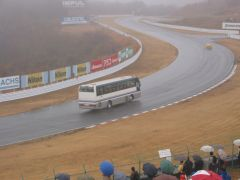 Bus on the track with the race cars